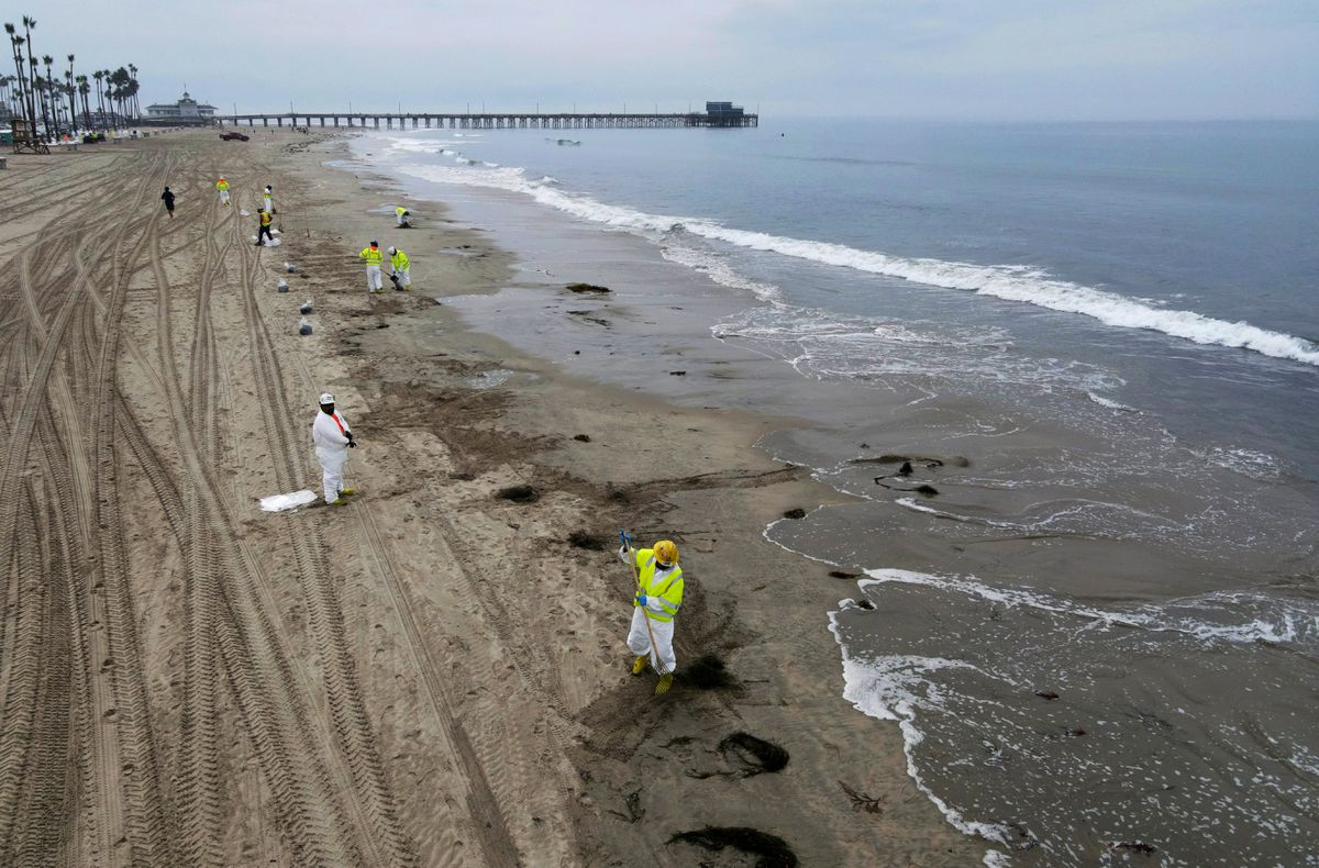 Workers rake up crude oil, after more than 3,000 barrels (126,000 gallons) of crude oil leaked from a ruptured pipeline